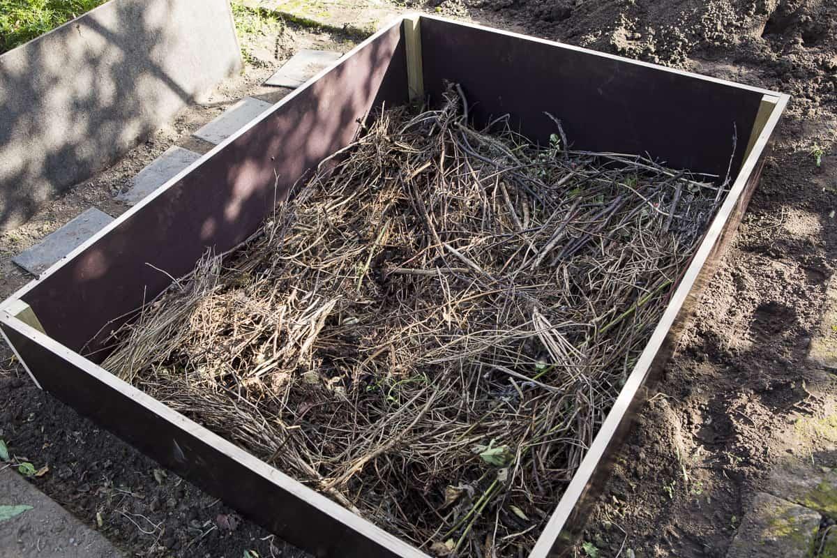 Hochbeet befüllen, erste Schicht Zweige, Äste, Heckenschnitt